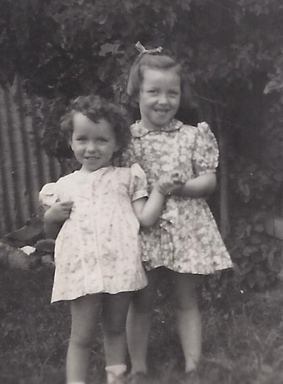 Faye and Carol in  summer dresses, Faye behind Carol and holding her hand