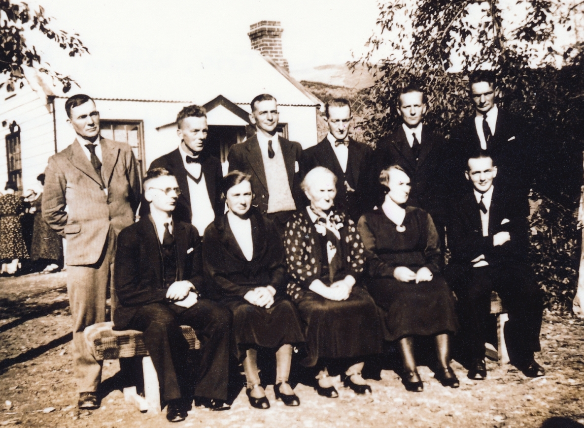 Family group  in a garden, two rows sitting and standing.