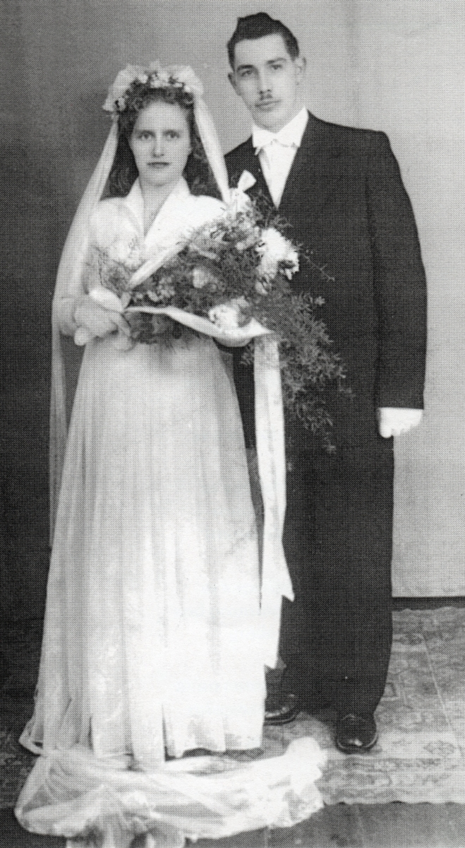 Full-length  studio shot of Antoni and Halina after their wedding. They seem serious.