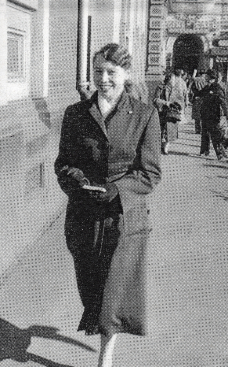 Henia striding   along a street, smiling widely and wearing a skirt suit