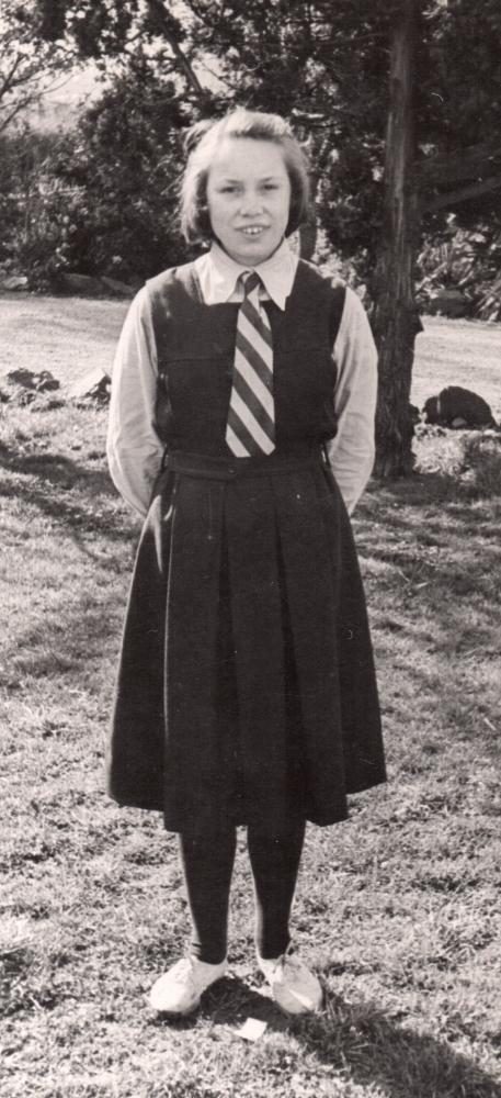 Henia in  school gymslip, white shirt and tie standing in the school gardens