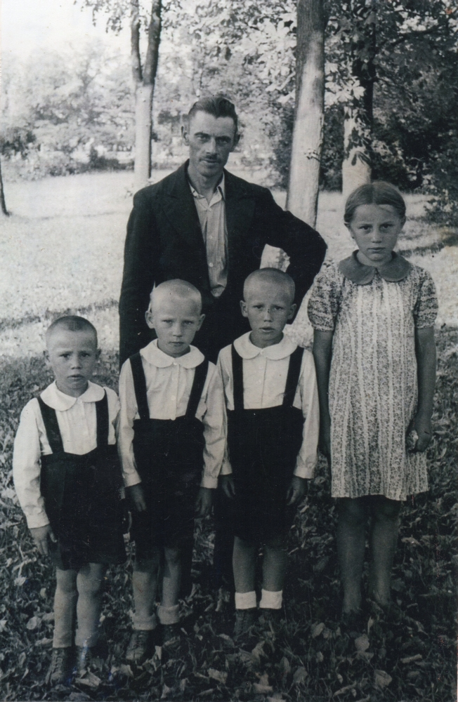 A photograph of Henryk standing with and four of his children, the boys dressed the same, in dark shorts and shirts and  Irena in a dress. Serious children.