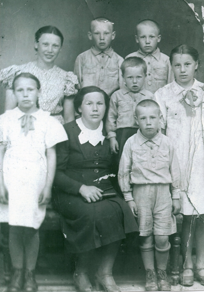 A studio  photograph of Waleria, sitting with a handbag on her lap and surrounded by her children