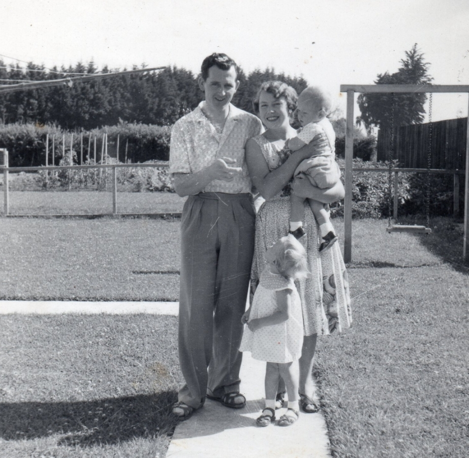 The young family  in the gardene on a sunny day. Halina is carrying the toddler Gary and Christine, about three, is looking up at her father