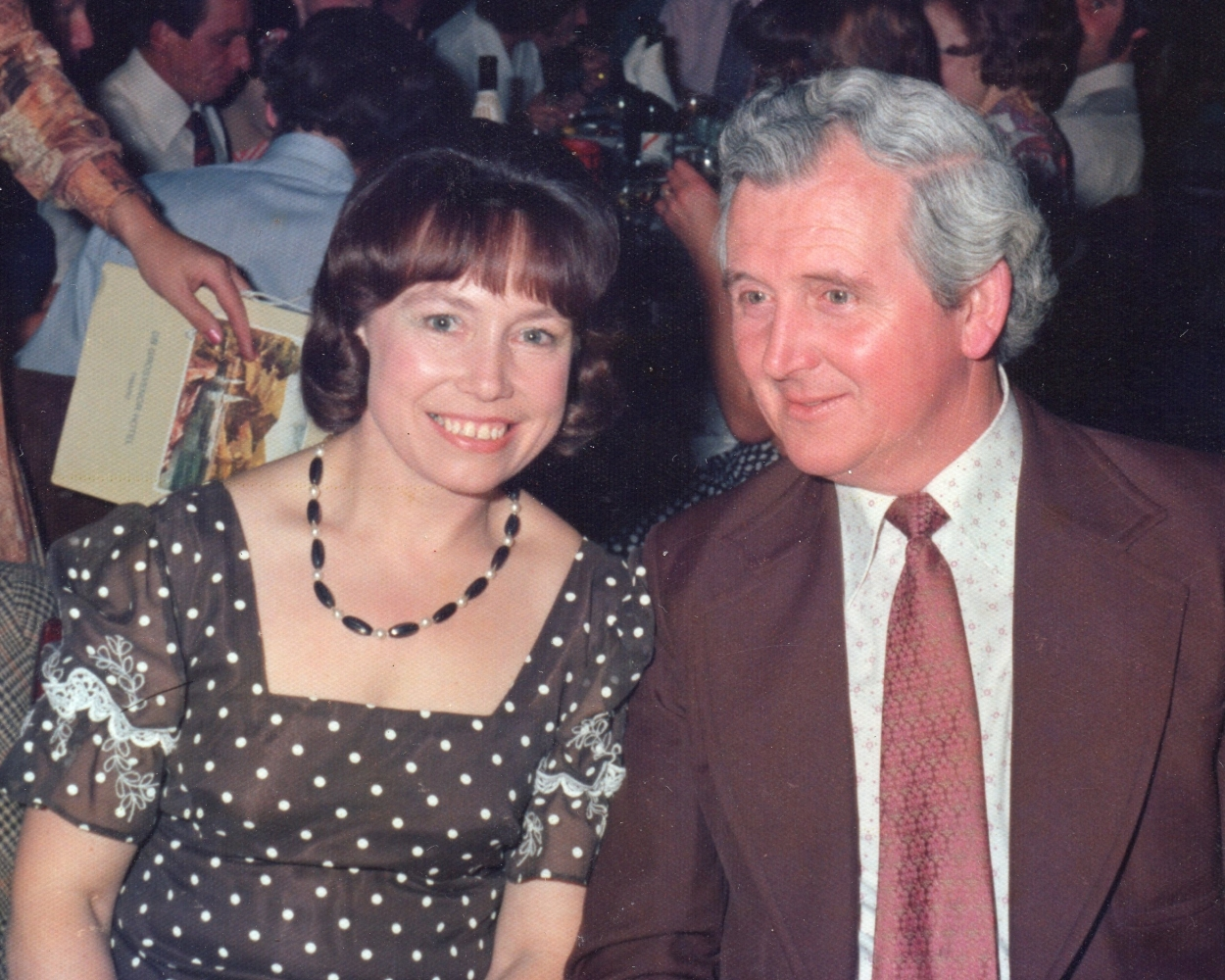 Henia and George  at a social function. Henia's dress is brown-dotted, square-necked and has intricate lace detail on the short sleeves
