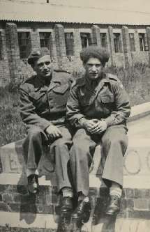 Bronisław Bojanowski with a friend sitting on a wall outside a barracks in England