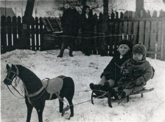 Jadzia and Jan  Jarka on a sled in the garden with their parents in the background