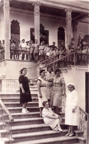 Group of boys and  their caregivers on steps outside Isfahan mansion