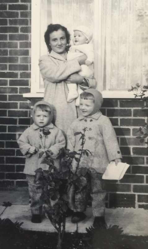 Joanna,  holding a baby with her sons in front of her, all dressed in coats.