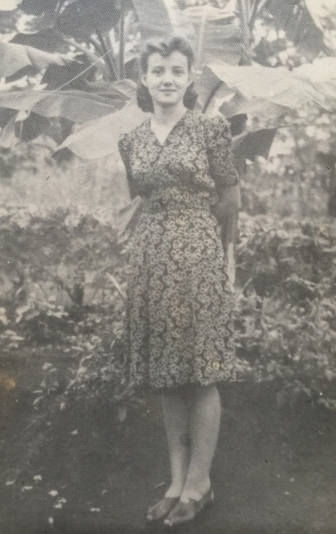 Joanna in  a dress, hands behind her back, standing in a garden.