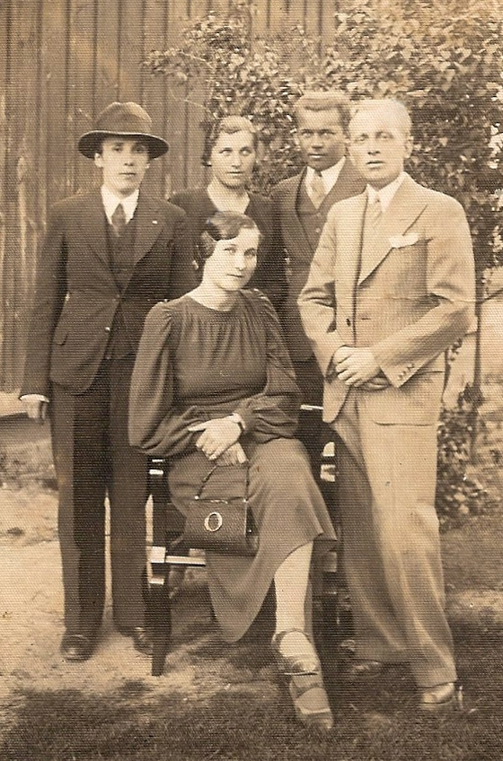 Bronisława  Meder sitting on a chair with four people standing behind her, Józef to the front right and her sister between the other two  men; photograph taken in a garden.