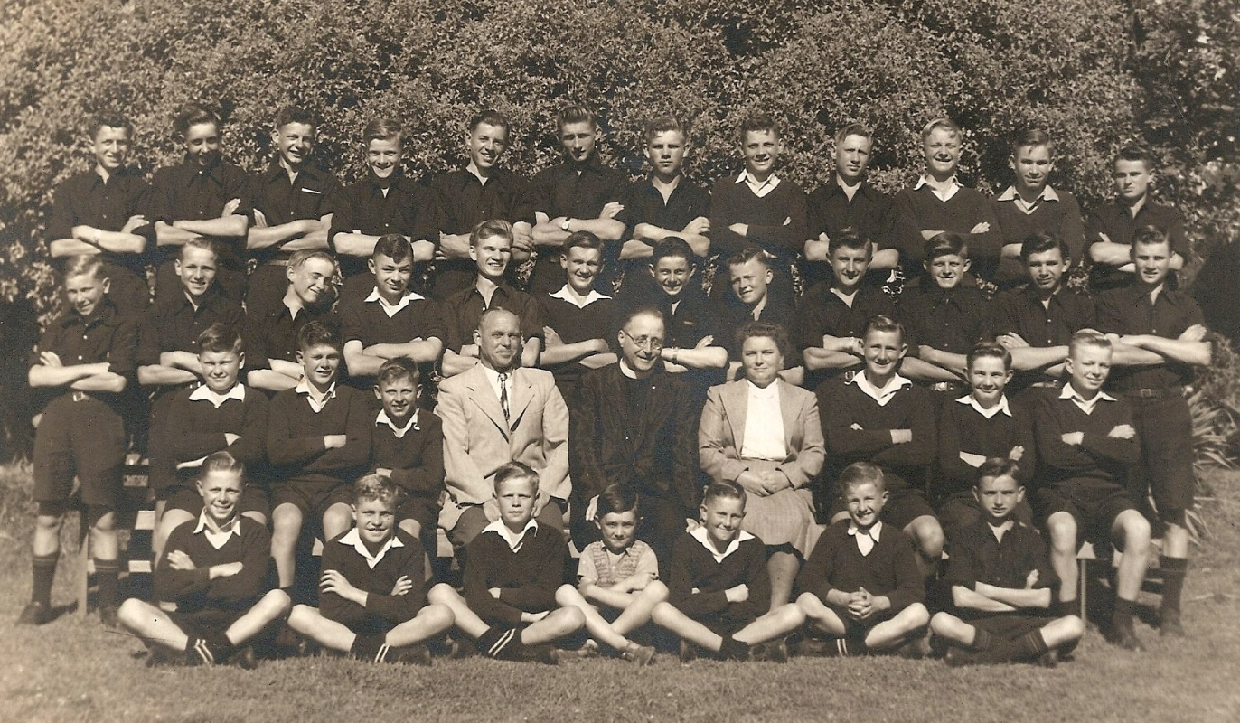 More formal group  photo, boys dressed in dark uniforms, all arms folded. Mr and Mrs Tietze in light clothes, priest sitting between them.