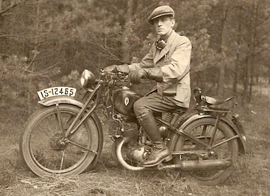 Josef sitting  on a motorbike, a wooded background. He is wearing a cap and light jacket, and has goggles around his neck and a black  rectangular camera bag attached to a strap that seems to hang from the unseen shoulder.