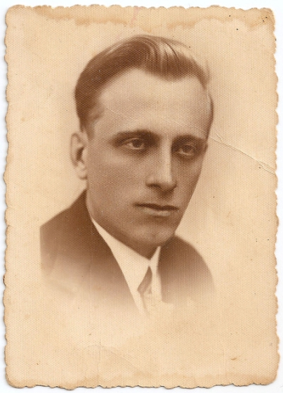 Studio head shot   Józef Zając in a dark suit, looking away from the camera, serious expression, darkened deep-set eyes, photo fading below the  tie-knot.