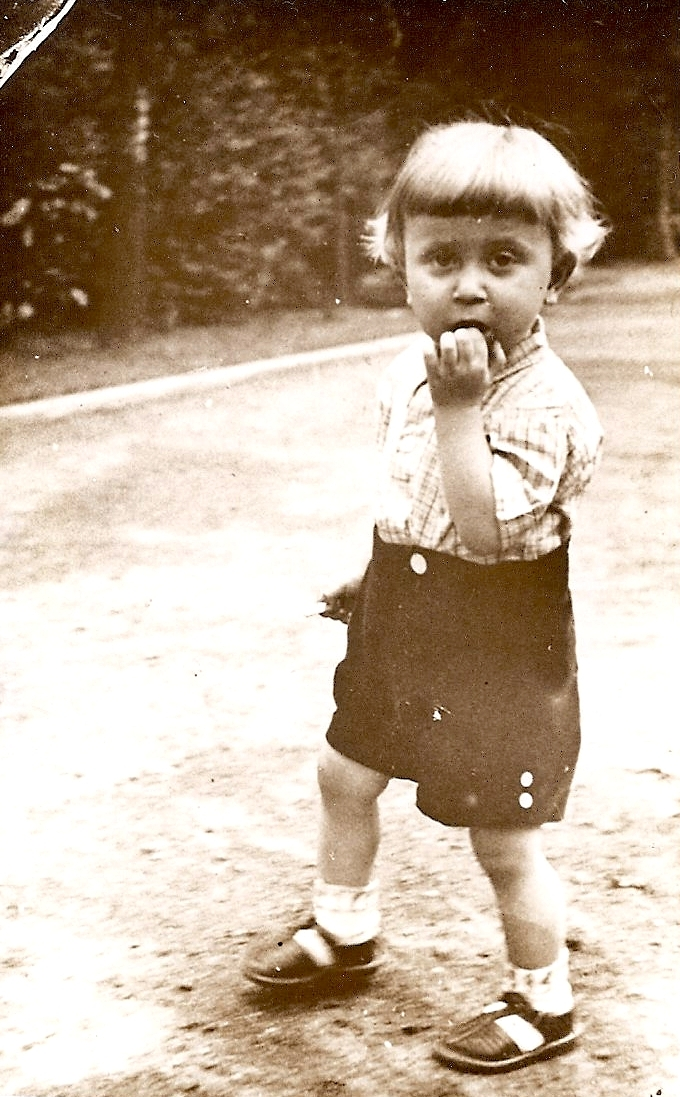 Blond Kazik  dressed in short-sleeved shirt and shorts, socks and sandals, hand in mouth but looking at the camera.