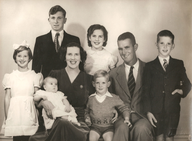 A studio photo  of Kazik and the Campbell family. Mr and Mrs Campbell and their three oldest children are all smiling widely: Kazik less so.  Baby on Mrs Campbell's lap and the second-youngest between his parents. Photo exudes positivity.
