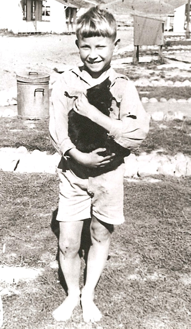Barefooted Kazik, in  shorts and a long-sleeved white open-neck shirt, holds the placid black cat and beams.