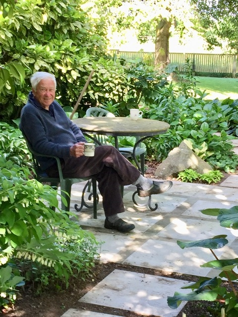 Kazik sitting at a  table in the garden with sloppy jumper, slippers and a mug in his hand; smiles at the camera.