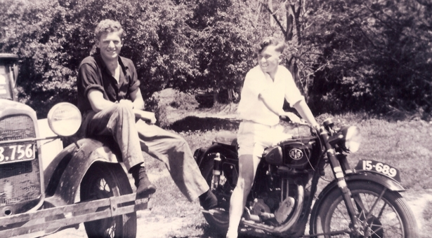 Kazik on his motorbike,  smiling at Jan, who is sitting on the wheel-rim of his car.