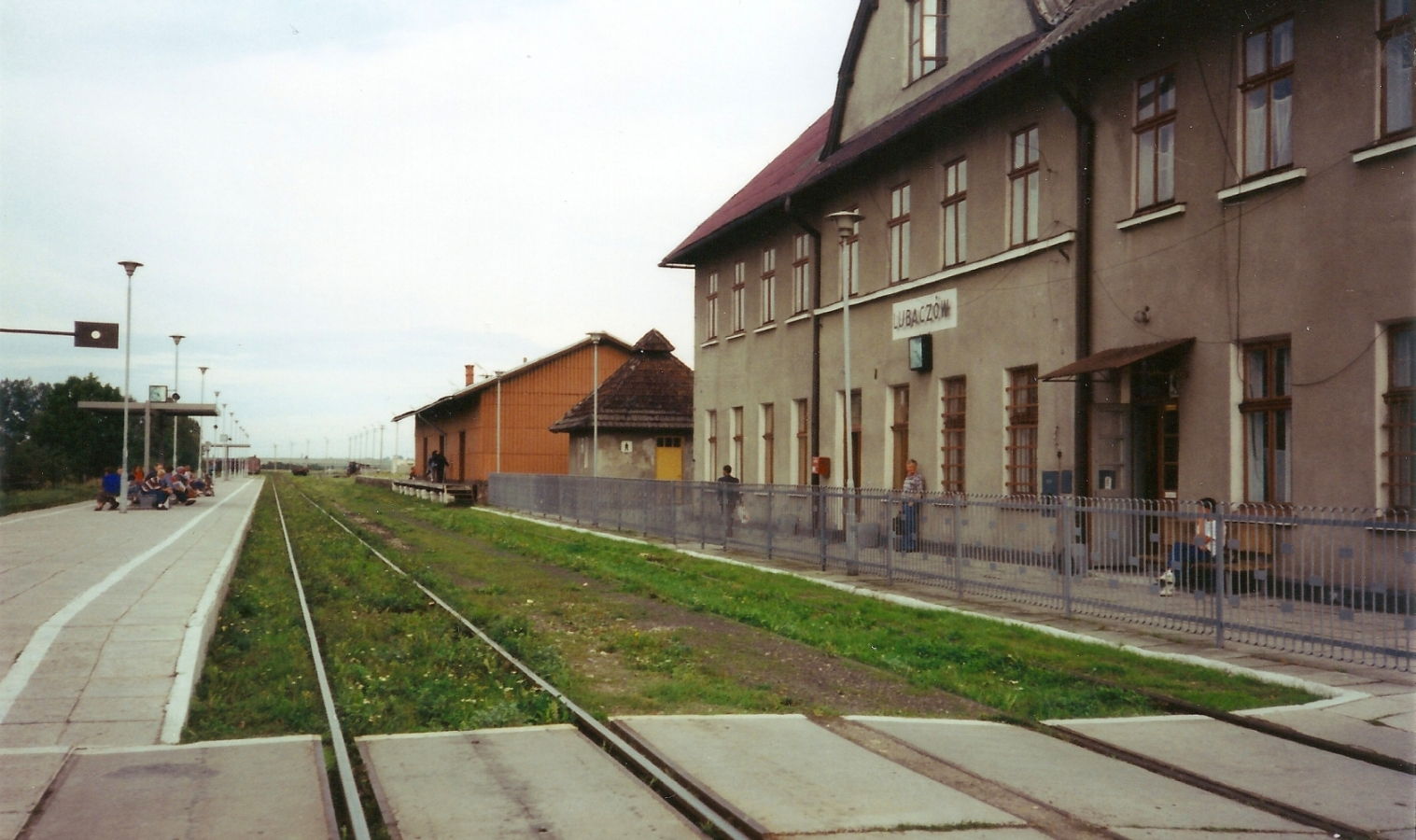 The outside  of Lubaczów railway station. Kazik stands under the station sign, small with the whole image.