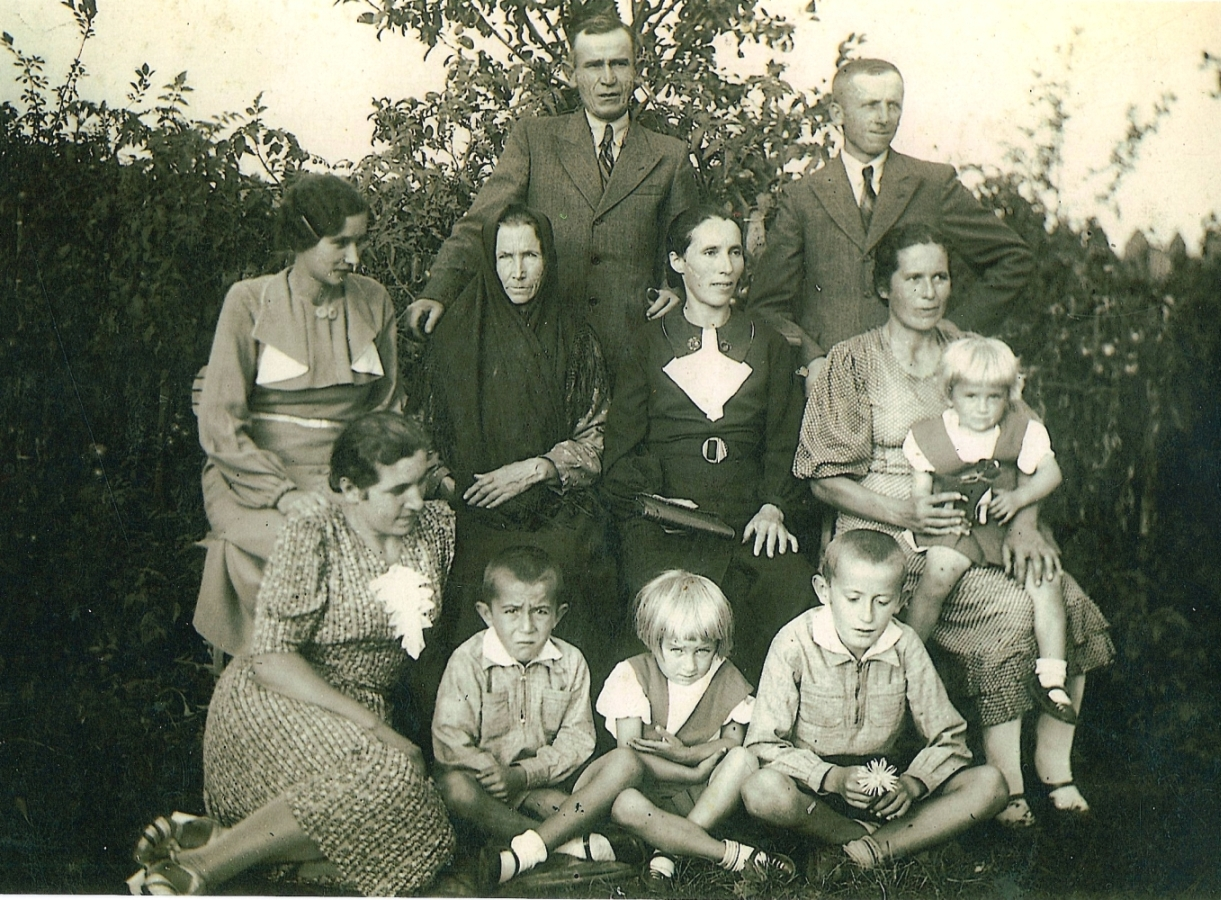 Maria Meder, severe  and dressed in black with a black scarf over her head, sits with her daughters, and grandchildren. Sons-in-law stand at back. Taken in a garden.