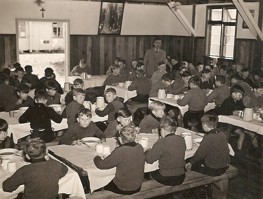 The inside of the  dining room, four rows of tables with bench-seats, white tablecloths and boys eating. A man is at the back.