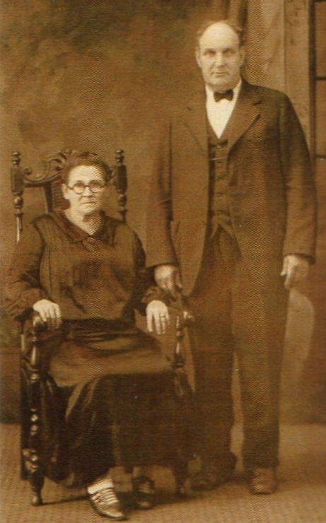 A  blurry studio photo of Johann and Augustine. He is standing, she is seated in a large chair