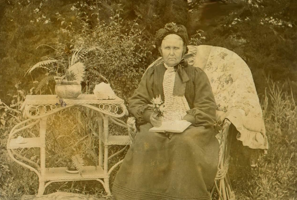 The old lady seated  on a wicker chair in the garden, next to a wicker table and with a book on her knee.