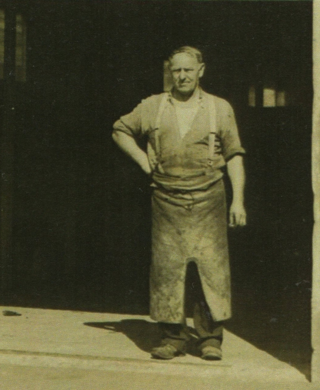 Michael Kowalewski,  in his blacksmith's apron in the doorway of his blacksmith's forge.