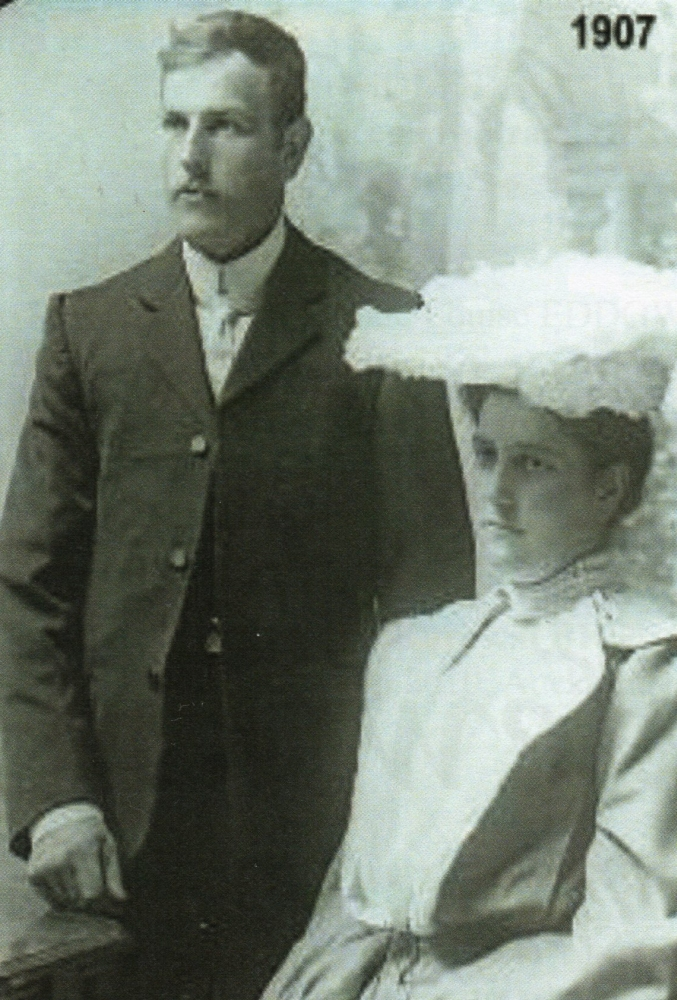 Michael and Clara on their wedding day. Clara is seated and they are both looking to the left.