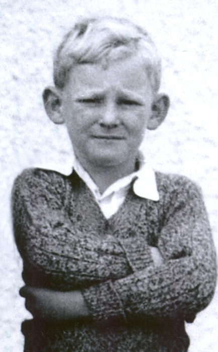 Allan  Hughes, arms crossed, staring into the camera, as a Standard One pupil in 1941