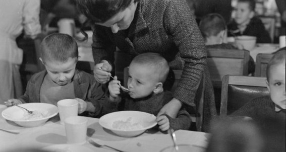 Three Polish   boys at a dining table, woman helping middle one to eat