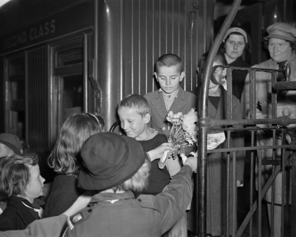 Some of the  Polish children on the train steps being greeted by Palmerston North children holding flowers