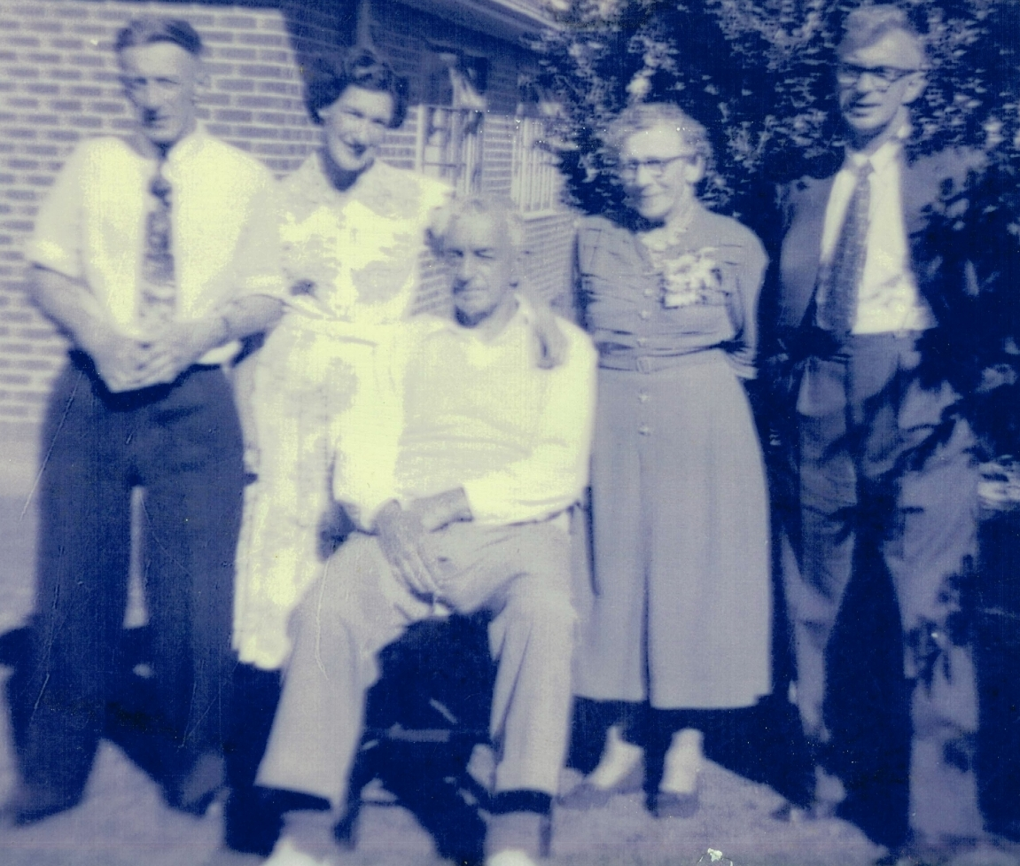 Taken outside a  house with Bert sitting, behind him are Alfred, Rona, with her arm around her father, Edith and Jack