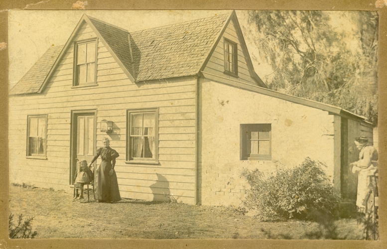 Wood and  sod house with two unknown woman and an unknown child