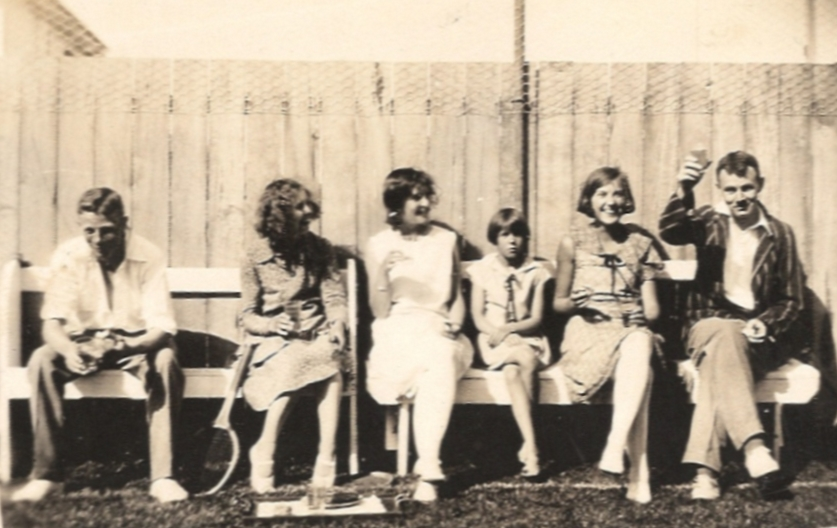 John Lovelock with Madeline, Rayena, a neighbour, Mavis and Don Sinclair junior sitting on a bench next to the tennis  court