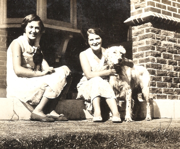 Gerturude and Mavis Orlowski on house steps with magpie and dog
