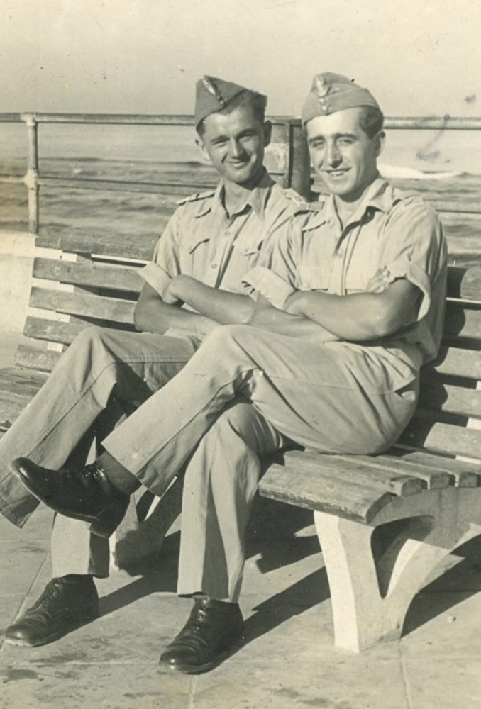 Władysław and a friend sit on a bench at the seaside