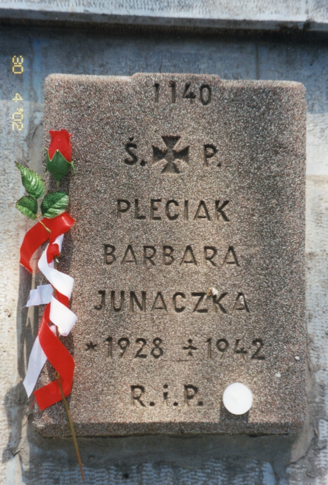 Barbara Pleciak's  headstone with a red rose, stem wrapped in red and white ribbon