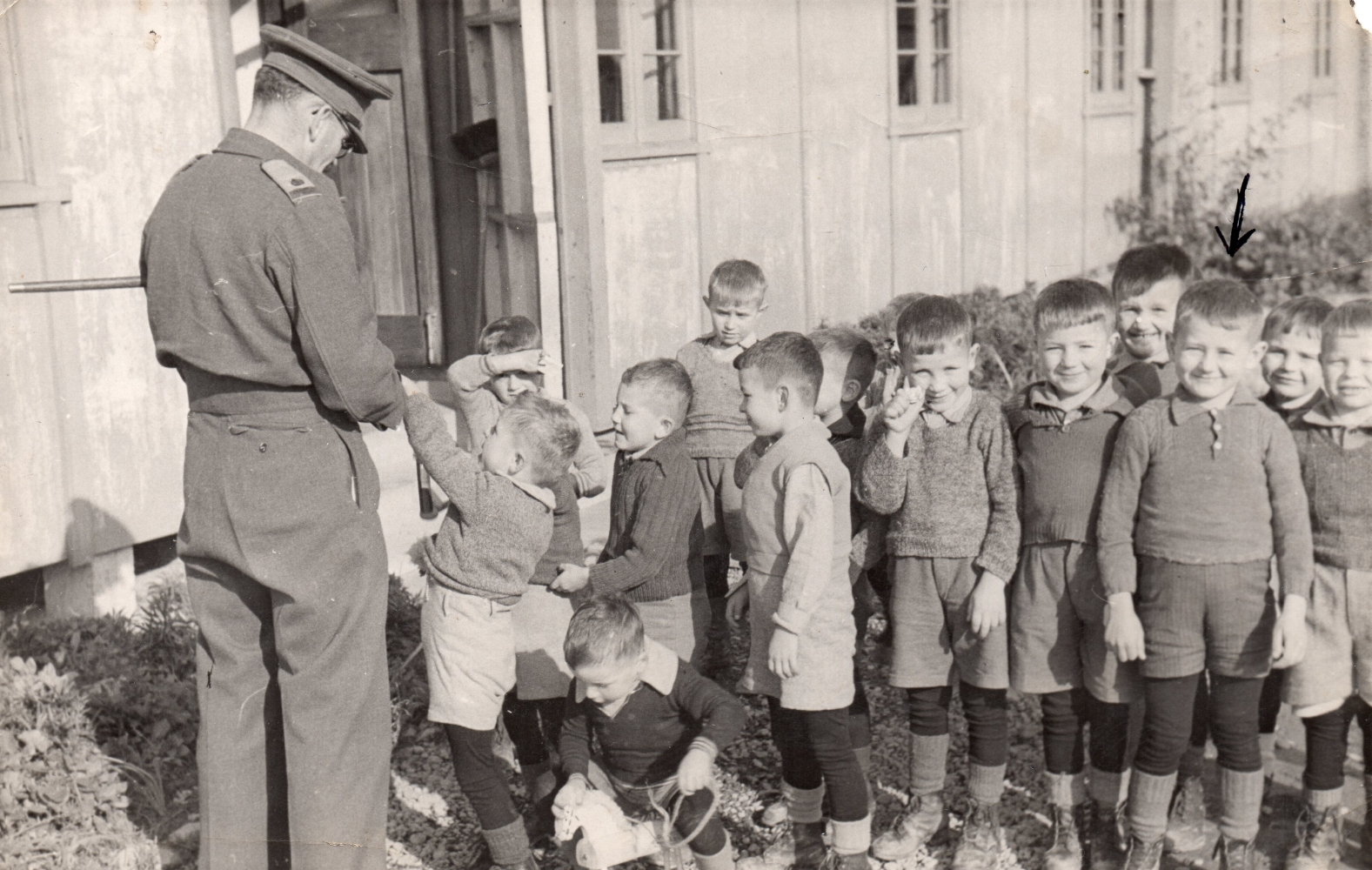 A soldier with  his back to the camera entertaining a group of boys.