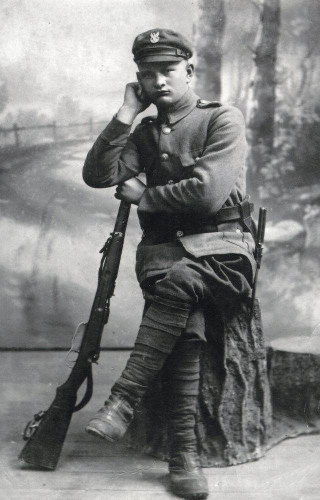 Studio pic of  Wojciech Pleciak, sitting and leaning on a rifle.