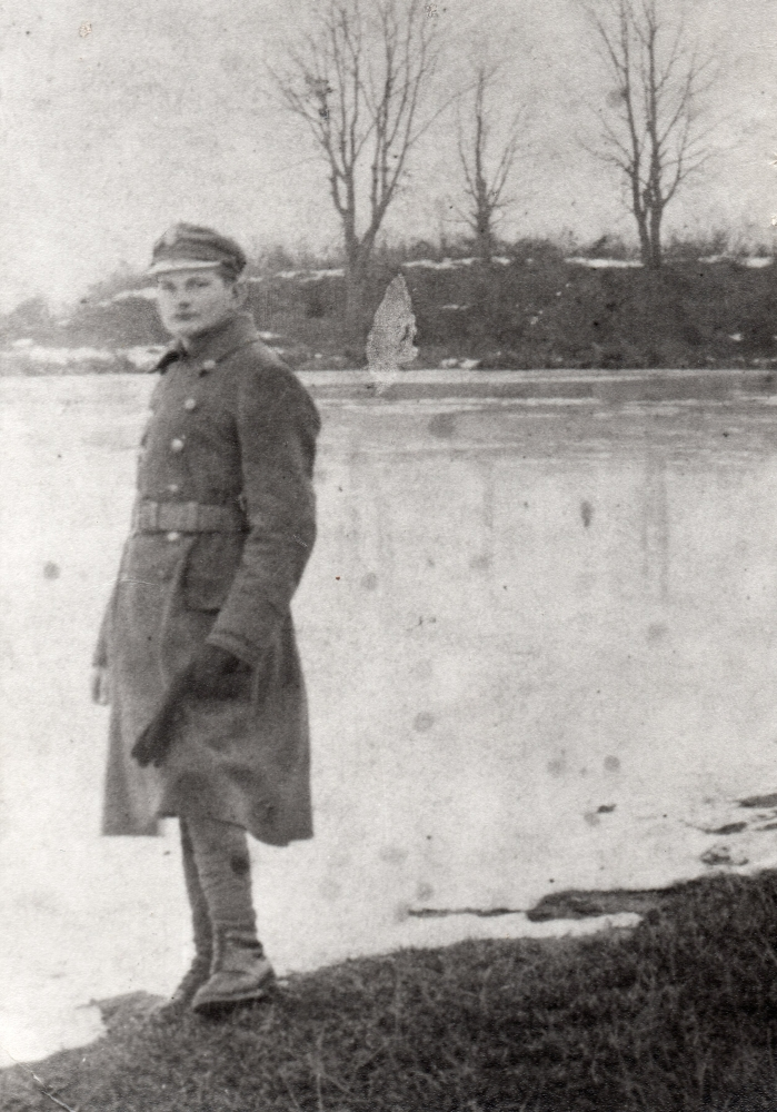 Wojciech Pleciak  standing on the edge of a lake in thick army coat, looks like snow, bare branches on trees