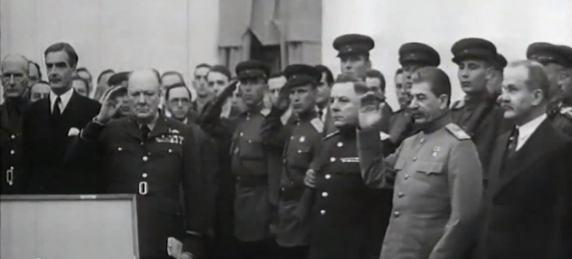 Stalin and Churchill  standing among military personnel and saluting the sword