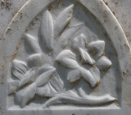 Close-up of  grey marble headstone, flowers
