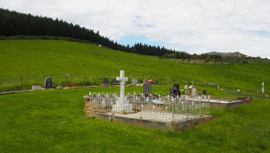 View of the  Waihola cemetery with Paul and Eva Baumgardt's gravesite, enclosed with a fence, in the foreground.