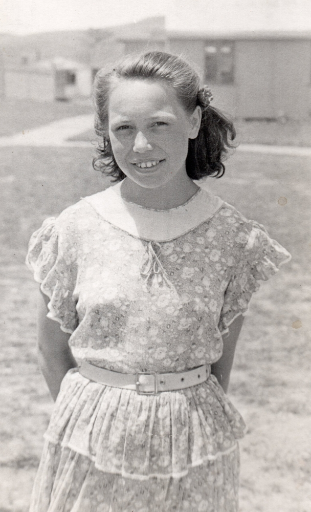 Henia  Aulich standing in a summer dress, outside, in Pahiatua. Barracks in background