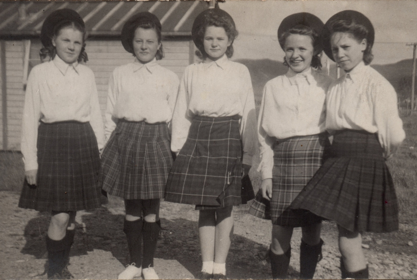The five girls   pose outside wearing their kilts, white shirts and Scottish berets