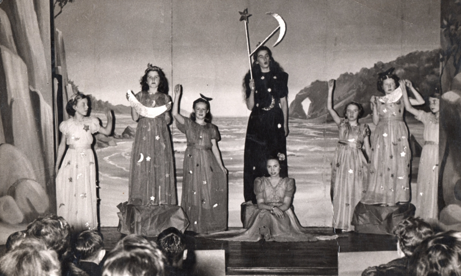 A scene on  stage at Villa Maria. Seven girls in long dresses are standing at the back and Henia is sitting serenely middle stage