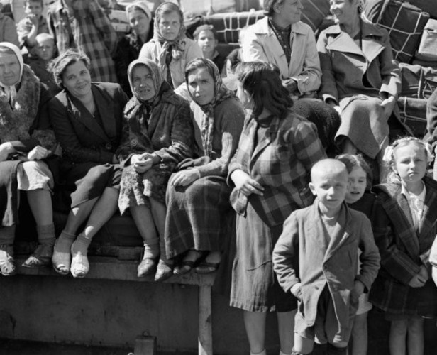 Older  Polish women sitting on deck with a shaved-headed boy in front with other cildren
