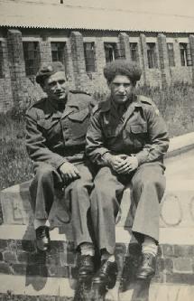 Bronisław Bojanowski with a friend sitting on a wall outside a barracks in England